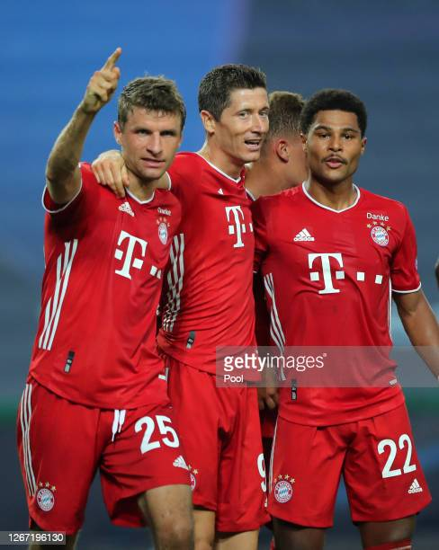 Serge Gnabry of Bayern Munich celebrates with teammates Robert Lewandowski of Bayern Munich and Thomas Mueller of Bayern Munich after scoring his...