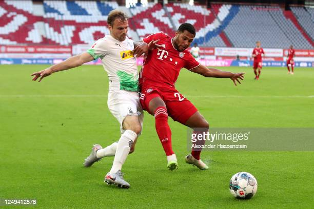 Serge Gnabry of Bayern Munich is challenged by Tony Jantschke of Borussia Monchengladbach during the Bundesliga match between FC Bayern Muenchen and...