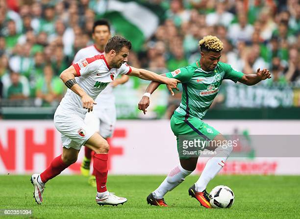 Serge Gnabry of Bremen is challenged by Daniel Baier of Augsburg during the Bundesliga match between Werder Bremen and FC Augsburg at Weserstadion on...