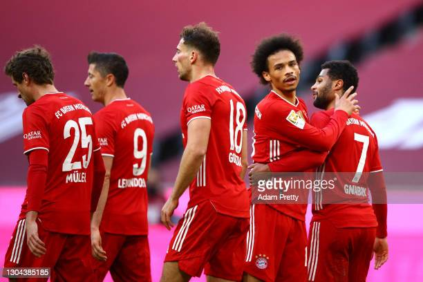Serge Gnabry of FC Bayern Muenchen celebrates with teammate Leroy Sane after scoring his team's fourth goal during the Bundesliga match between FC...
