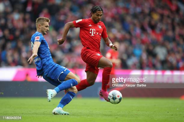 Serge Gnabry of FC Bayern Muenchen challenges Stefan Posch of TSG 1899 Hoffenheim during the Bundesliga match between FC Bayern Muenchen and TSG 1899...