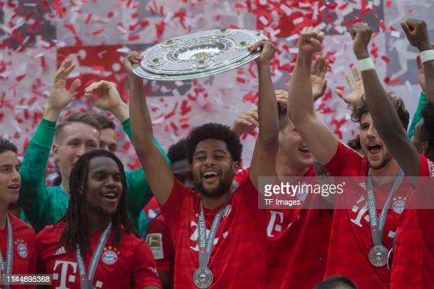 Serge Gnabry of FC Bayern Muenchen with the championship trophy after the Bundesliga match between FC Bayern Muenchen and Eintracht Frankfurt at...