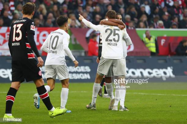 Serge Gnabry of FC Bayern Munich celebrates with teammate Thomas Muller after scoring his team's third goal during the Bundesliga match between...