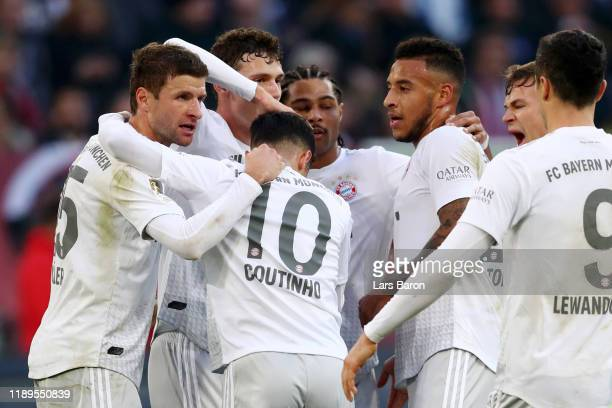 Serge Gnabry of FC Bayern Munich celebrates with teammates after scoring his team's third goal during the Bundesliga match between Fortuna...