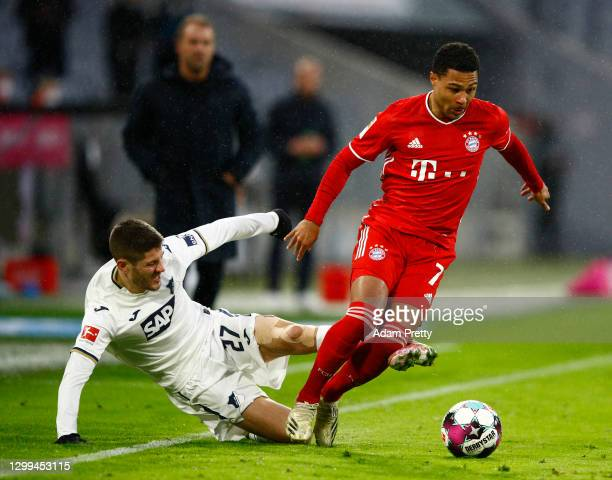 Serge Gnabry of FC Bayern Munich is challenged by Andrej Kramaric of TSG 1899 Hoffenheim during the Bundesliga match between FC Bayern Muenchen and...