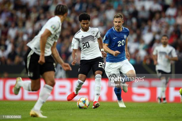 Serge Gnabry of Germany avoids Artjom Dmitrijev of Estonia during the UEFA Euro 2020 Qualifier match between Germany and Estonia at Opel Arena on...