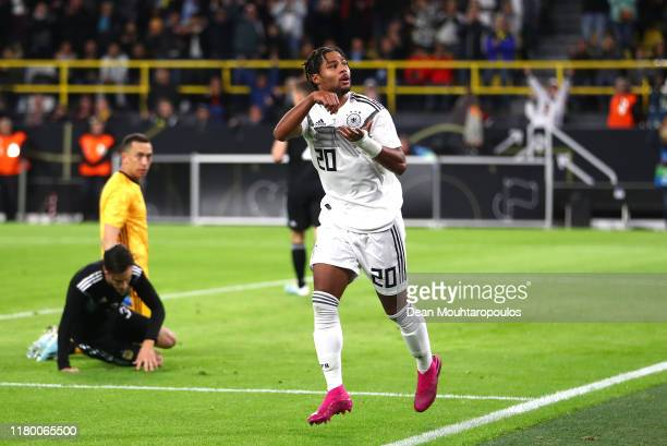 Serge Gnabry of Germany celebrates after he scores his sides first goal under pressure from Jonas Hector of Germany during the International Friendly...