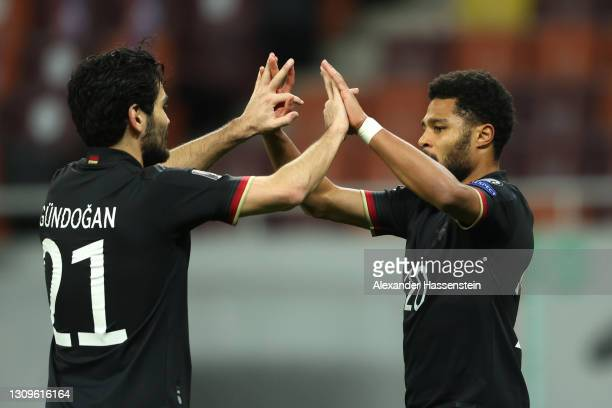 Serge Gnabry of Germany celebrates with team mate Ilkay Gundogan after scoring their side's first goal during the FIFA World Cup 2022 Qatar...