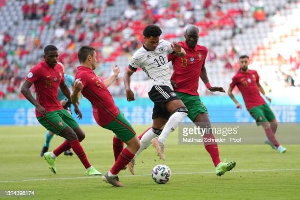Serge Gnabry of Germany is challenged by Raphael Guerreiro and Danilo of Portugal during the UEFA Euro 2020 Championship Group F match between...
