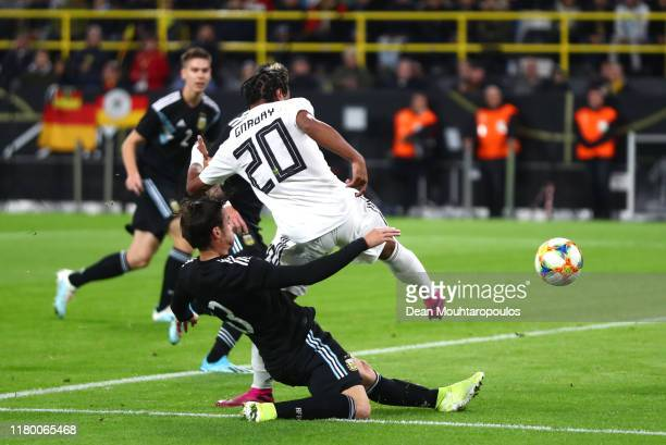 Serge Gnabry of Germany scores his sides first goal under pressure from Jonas Hector of Germany during the International Friendly between Germany and...