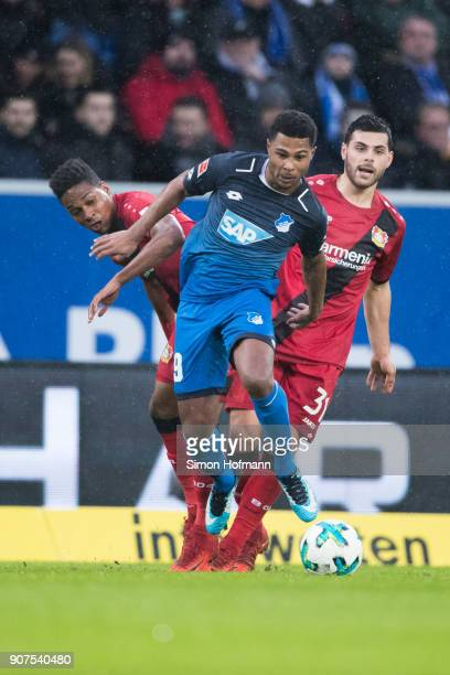 Serge Gnabry of Hoffenheim is challenged by Kevin Volland of Leverkusen and Leon Bailey during the Bundesliga match between TSG 1899 Hoffenheim and...