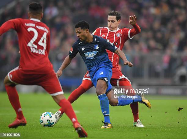 Serge Gnabry of Hoffenheim runs with the ball past Sebastian Rudy of Bayern Muenchen and Tolisso of Bayern Muenchen during the Bundesliga match...