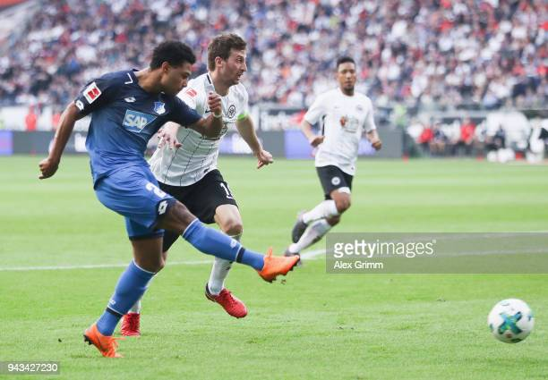 Serge Gnabry of Hoffenheim scores his team's first goal past David Abraham of Frankfurt during the Bundesliga match between Eintracht Frankfurt and...