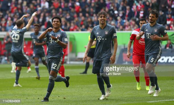 Serge Gnabry of Muenchen celebrates scoring his team's third goal with Javi Martínez and Mats Hummels during the Bundesliga match between Fortuna...