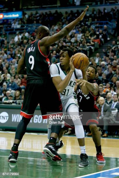 Serge Ibaka and Kyle Lowry of the Toronto Raptors guard against John Henson of the Milwaukee Bucks in the second quarter in Game Six of the Eastern...