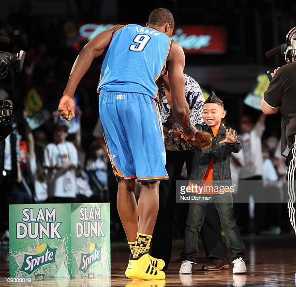 Serge Ibaka of the Oklahoma City Thunder hands a little boy a teddy bear during the 2011 Sprite Slam Dunk Contest at Staples Center on February 19...