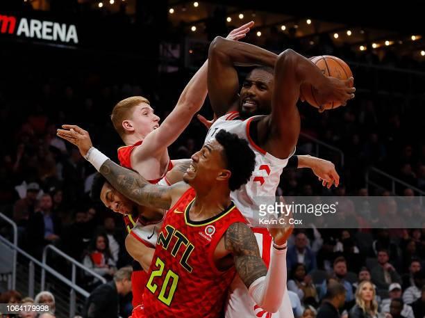 Serge Ibaka of the Toronto Raptors grabs a rebound against John Collins and Kevin Huerter of the Atlanta Hawks at State Farm Arena on November 21...
