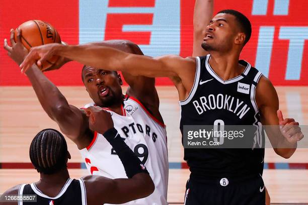 Serge Ibaka of the Toronto Raptors grabs a rebound against Timothe Luwawu-Cabarrot and Caris LeVert of the Brooklyn Nets during the third quarter in...