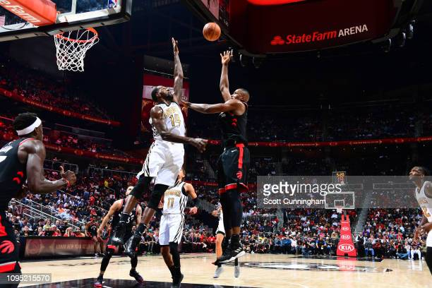 Serge Ibaka of the Toronto Raptors shoots the ball over Dewayne Dedmon of the Atlanta Hawks on February 7 2019 at State Farm Arena in Atlanta Georgia...