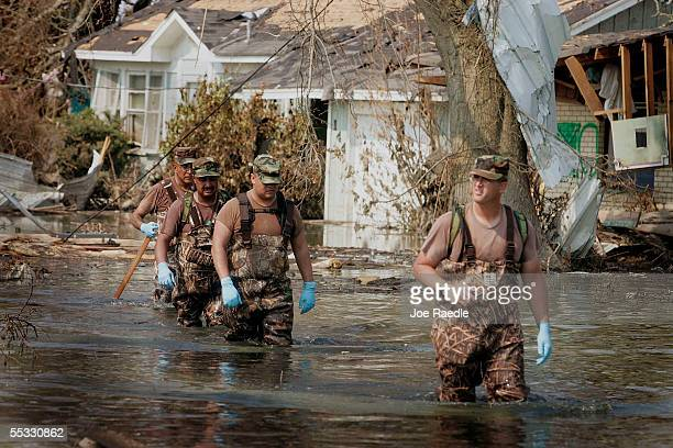 Sergeant 1st Class Chris Andrews from the New Mexico National Guard balances himself as he makes his way through water and debris to check for bodies...
