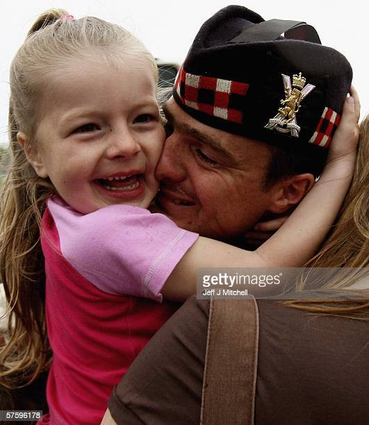 Sergeant Dean Fraser kisses his daughter Amy as The Royal Scots Battalion are seen returning at Dreghorn Barracks May 122006 in Edinburgh ScotlandThe...