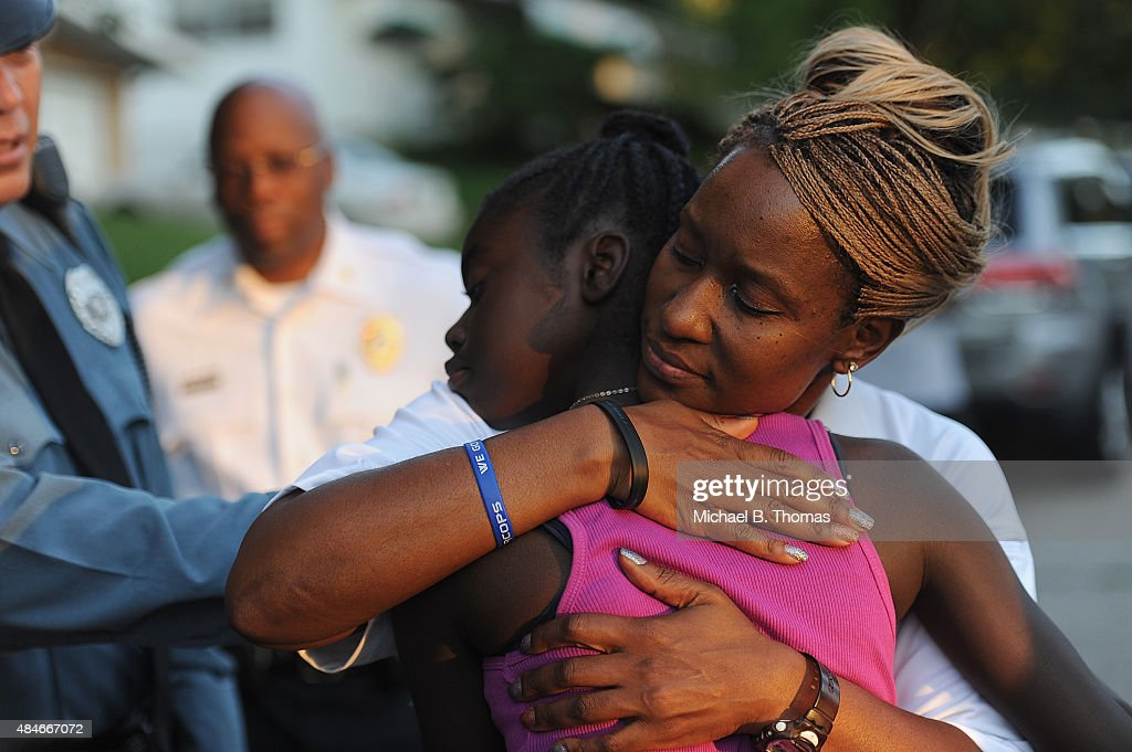 Sergeant Dominica Fuller consoles a mourning child during a candlelight vigil held in honor of Jamyla Bolden on August 20, 2015 in Ferguson, Missouri. Jamyla Bolden, 9, was allegedly struck by a stray bullet from a drive-by shooting and killed while doing her homework at her home in Ferguson on August 18th.