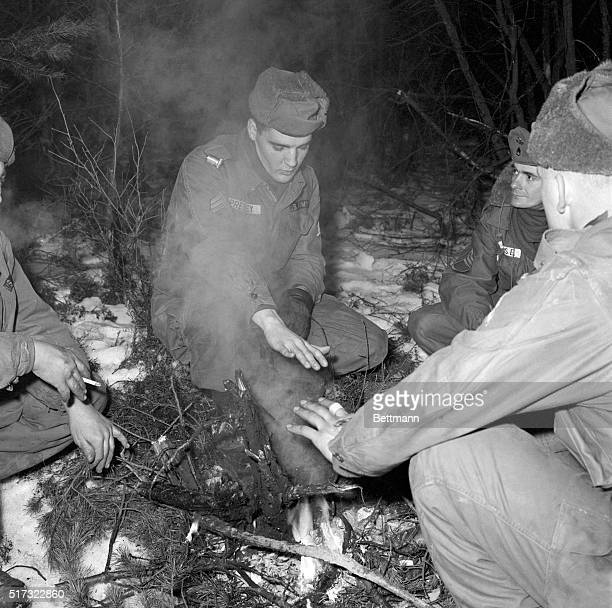 Sergeant Elvis Presley warms his hands by a fire while on maneuvers in West Germany, about a month prior to his discharge. 1960. | Location:...