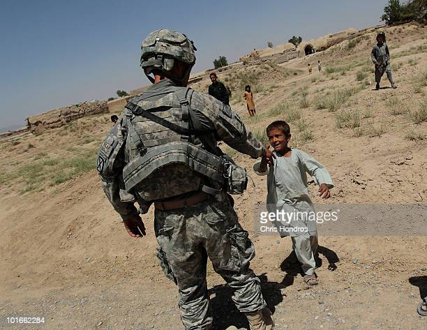 Sergeant First Class Joseph Denny of Franklin Indiana shakes hands with an Afghan boy during a patrol on June 6 2010 in Rambazi a village south of...