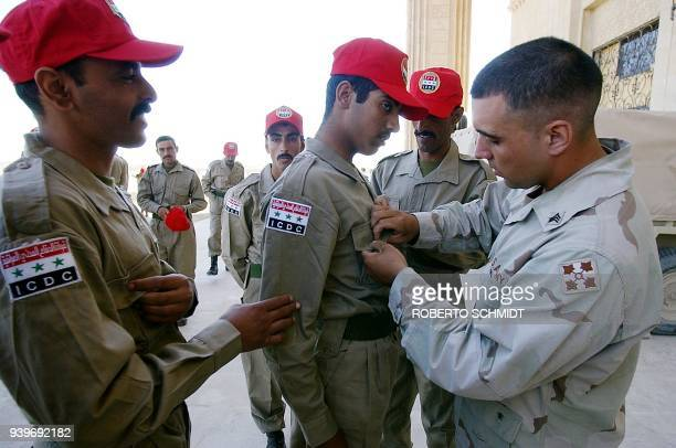 Sergeant Garza a US soldier from the 1st battalion 22nd infantry regiment 4th ID helps an Iraqi cadet with his uniform before he and 30 others...