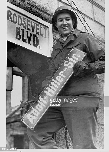 Sergeant George A Kaufman changes a street sign from Adolf Hitler Strasse to Roosevelt Boulevard in Krefeld Germany after his Ninth Army unit...