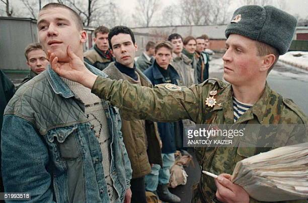"""Sergeant in the Russian army uses his hand to instruct the correct procedure and head position to fulfill the """"eyes right"""" command to a young recruit..."""