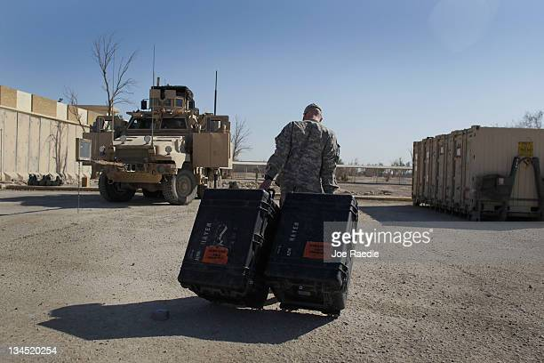 Sergeant Jeffrey Merrick from Columbus, Ohio of the 2-82 Field Artillery, 3rd Brigade, 1st Cavalry Division, pulls cases of equipment to a shipping...