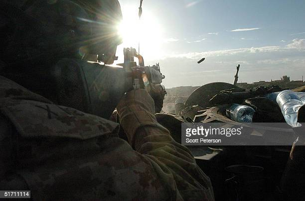 Sergeant Kevin Boyd fires at targets as US Marine scouts of the Light Armor Reconnaissance prepare to move November 9 2004 into Fallujah Iraq On the...