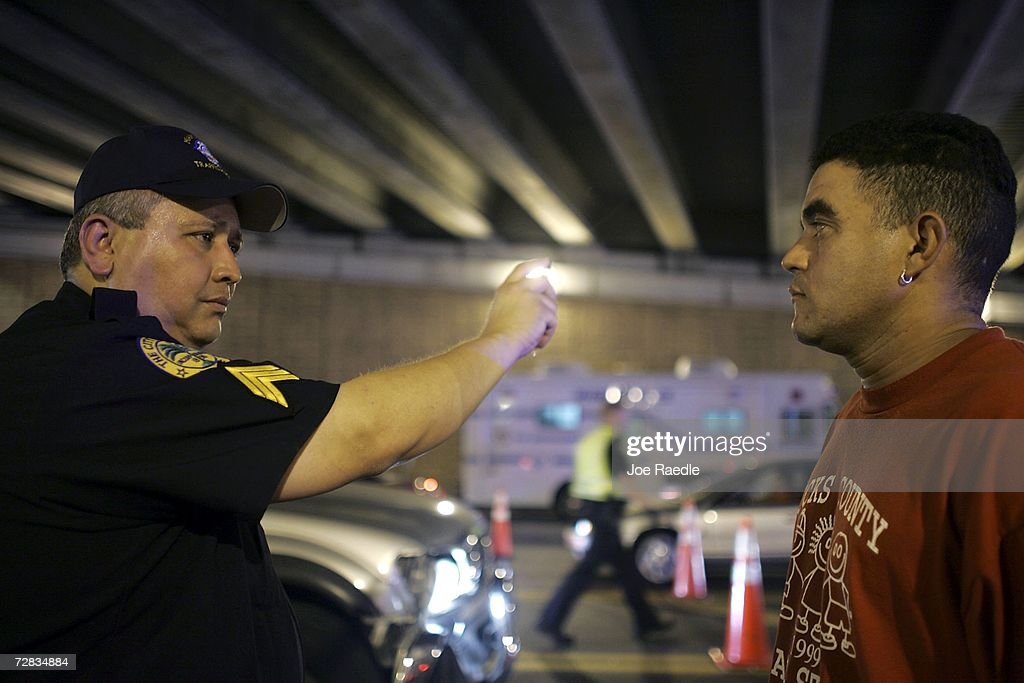 Sergeant Luis Taborda from the City of Miami police department (L) conducts a field sobriety test at a DUI checkpoint December 15, 2006 in Miami, Florida. The city of Miami, with the help of other police departments, will be conducting saturation patrols and setting up checkpoints during the holiday period looking to apprehend drivers for impaired driving and other traffic violations.