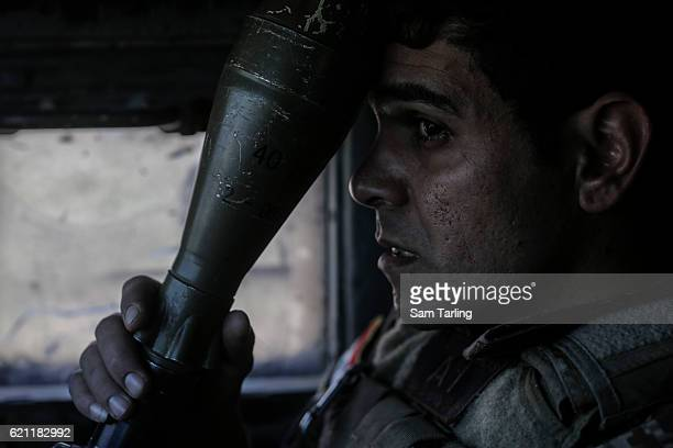 Sergeant Majid holds a rocket propelled grenade as his Humvee approaches the neighborhood of Tahrir and Zahara, formerly named after Saddam Hussein,...