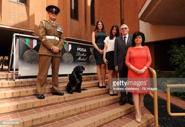 Sergeant Major Andy Dodds joins members of Lance Corporal Rowe's family in standing with Labrador Fire as she wears a replica of the PDSA Dickin...