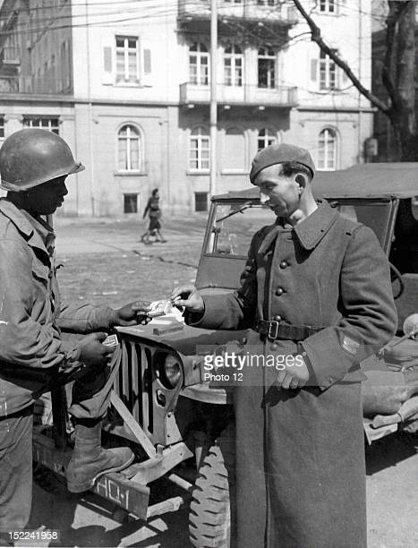 A sergeant of the 139th Reg d'Infanterie de Forteresse on his way home after five years as a prisonner in Germany accepts a cigarette from an US...