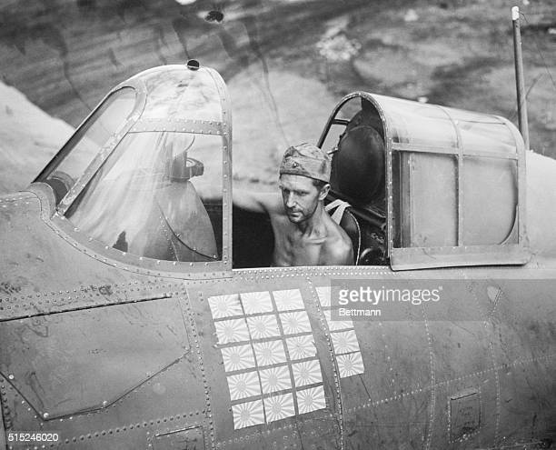 Sergeant RW Greenwood sits in his Grumman F6F Hillcat at Henderson Field Guadalcanal The plane is marked with 19 Japanese flags one for each enemy...