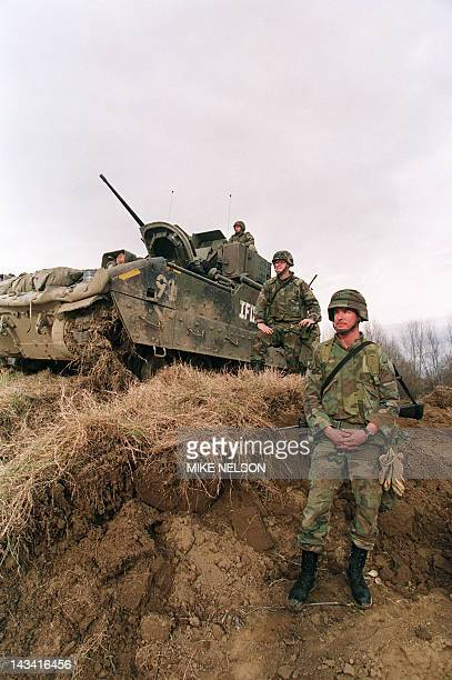 Sergeant Steve Norris from Pismo Beach California and Lt Jeff Schall from Pittsburg stand guard next to their Bradley fighting vehicle as work on the...