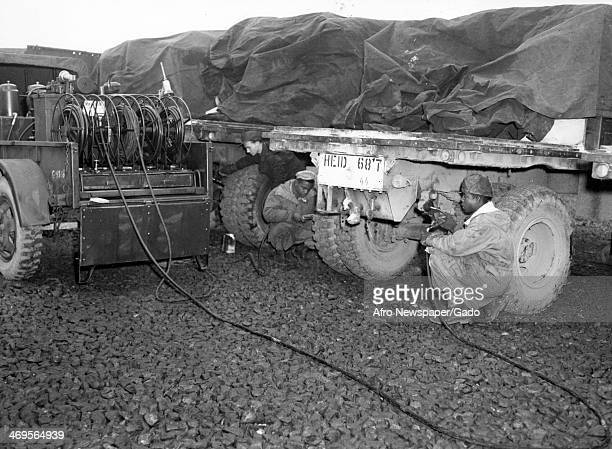 Sergeant Thomas Tyler and Rct R W Walker operate a mobile lubrication unit which is used to service Army ten ton trailers used in transporting food...