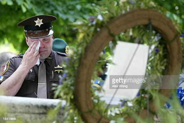 Sergeant Tony Grahovac of the sheriff department of Munising, Michigan, wipes his eyes as he moums the loss of his brother who was killed while...