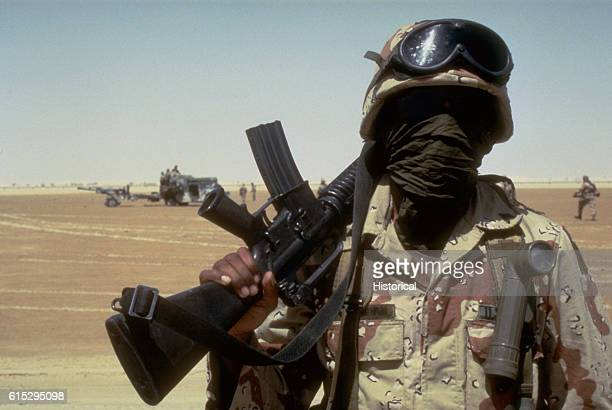 A sergeant with the 82nd Airborne Division wears a kerchief and sunglasses to help protect him from the dust and bright sun of the Saudi desert...