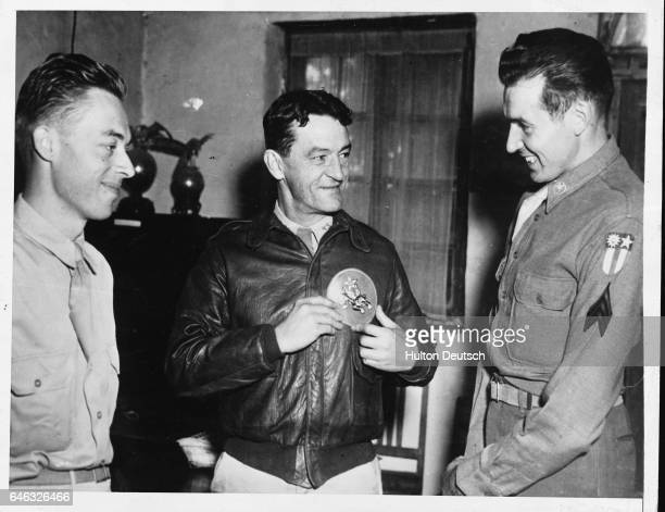 Sergeants Howard Arnegard and Robert Naves present Major General Claire Chennault , the commander of the Flying Tigers of the 14th Air Force, with an...