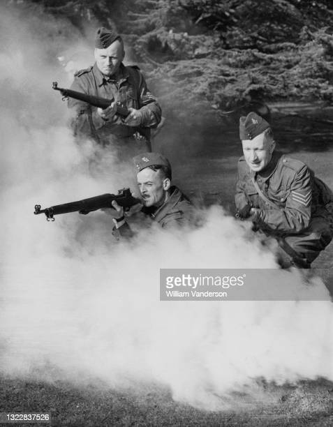 Sergeants of the Local Defense Volunteers Home Guard undertake rifle drill training with the Pattern 1914 Enfield bolt action rifle through a smoke...