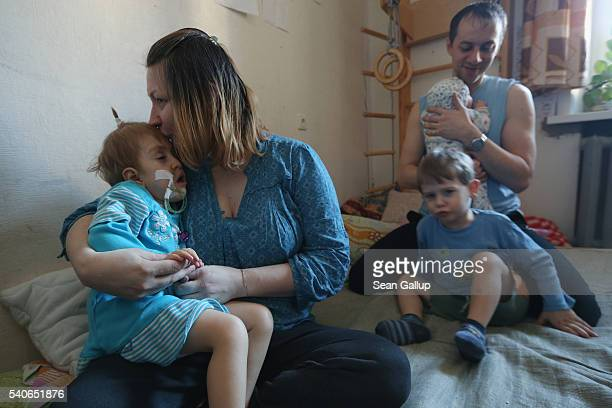 Sergei and Ina Chalyadinsky cuddle with their children including severelyhandicapped Liza healthy Artiom and healthy baby Styopa at their apartment...