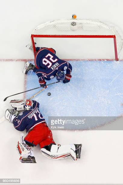 Sergei Bobrovsky of the Columbus Blue Jackets and Thomas Vanek of the Columbus Blue Jackets attempt to gain control of a loose puck in Game Four of...