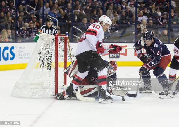 Sergei Bobrovsky of the Columbus Blue Jackets attempts to cover the puck while Blake Coleman of the New Jersey Devils and Scott Harrington of the...