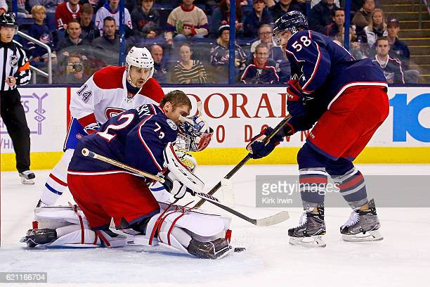 Sergei Bobrovsky of the Columbus Blue Jackets looses his helmet while stopping a shot from Tomas Plekanec of the Montreal Canadiens as David Savard...