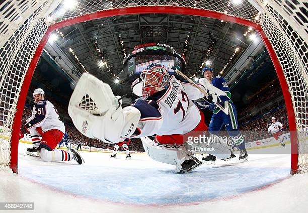 Sergei Bobrovsky of the Columbus Blue Jackets reaches back to make a save as Fedor Tyutin of the Columbus Blue Jackets and Jannik Hansen of the...