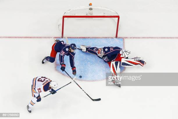 Sergei Bobrovsky of the Columbus Blue Jackets stops a shot from Ryan NugentHopkins of the Edmonton Oilers as Alexander Wennberg of the Columbus Blue...